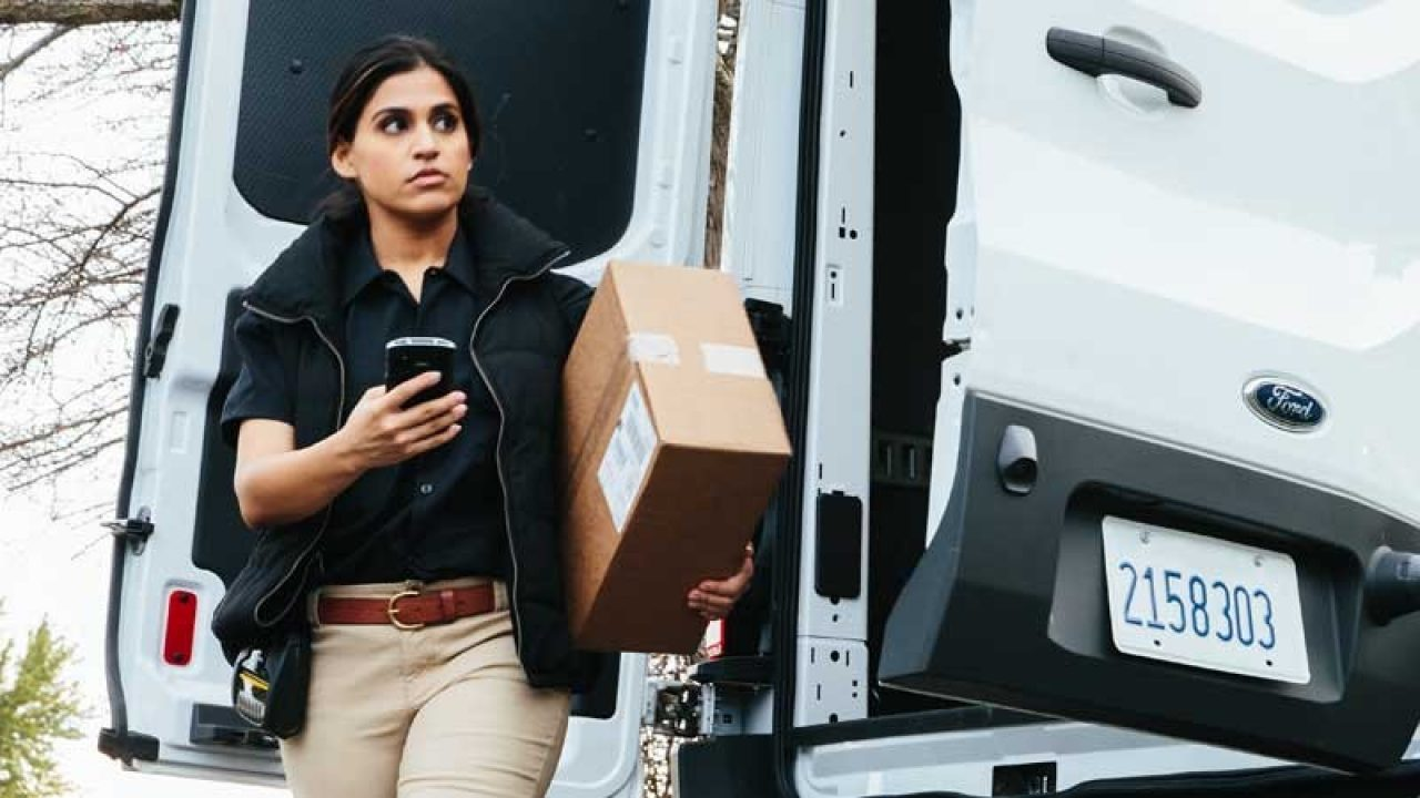 Lady parcel carrier with package checking mobile device from the delivery truck.