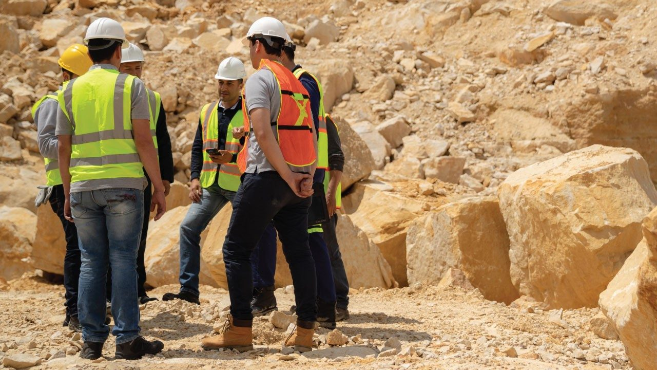 A group of workers wearing a hardhats and safety vests by rocks.