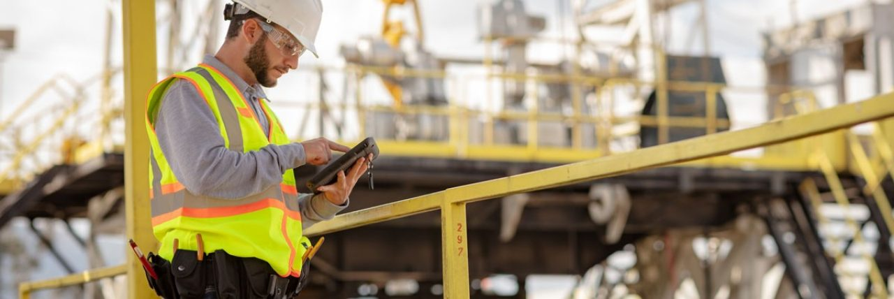Energy company employee wearing a hardhat and using a tablet.