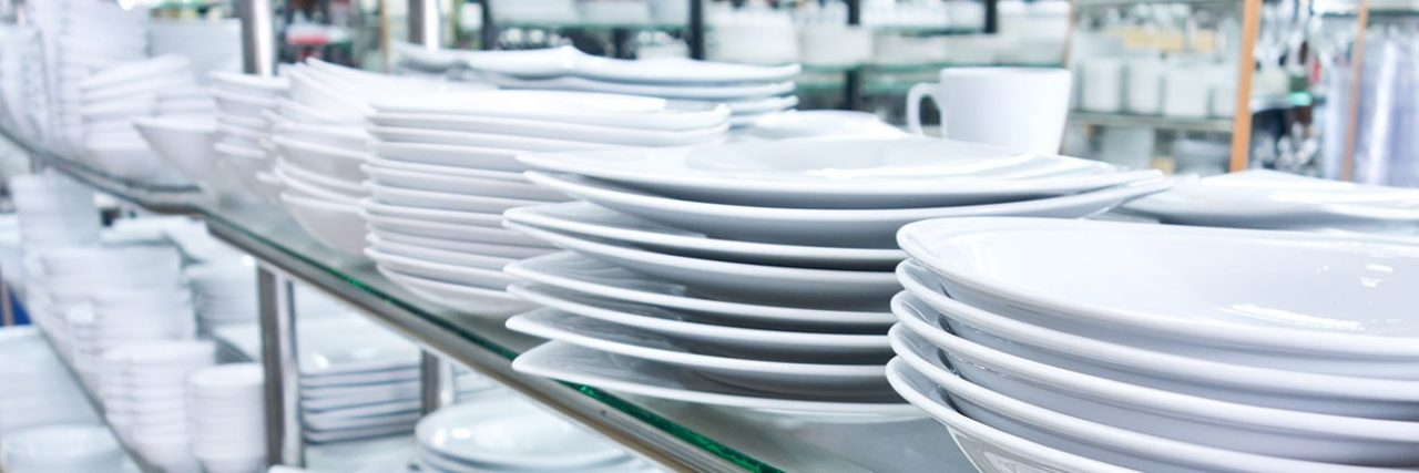 stacks of clean dish\u002Dware in a restaurant kitchen