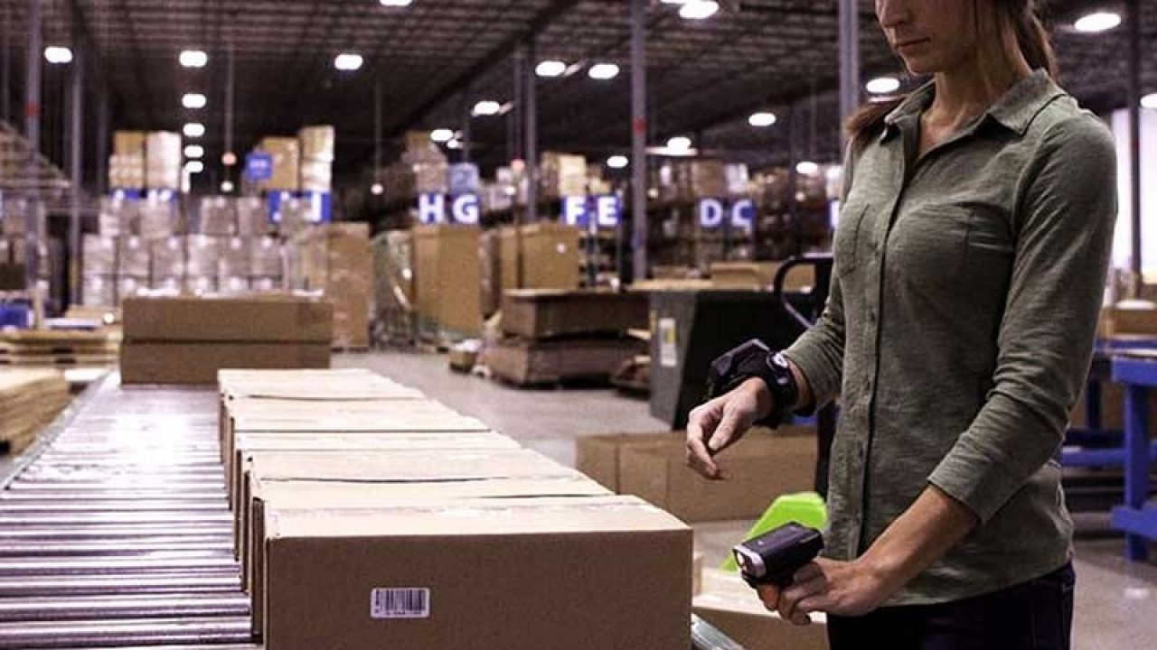 Woman Scanning boxes on product line