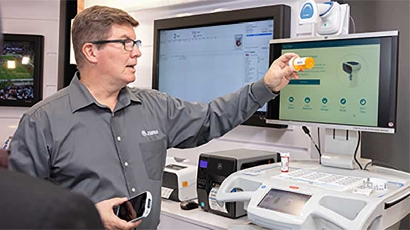 man holding up prescription bottle for while holding healthcare scanner in zebra experience center