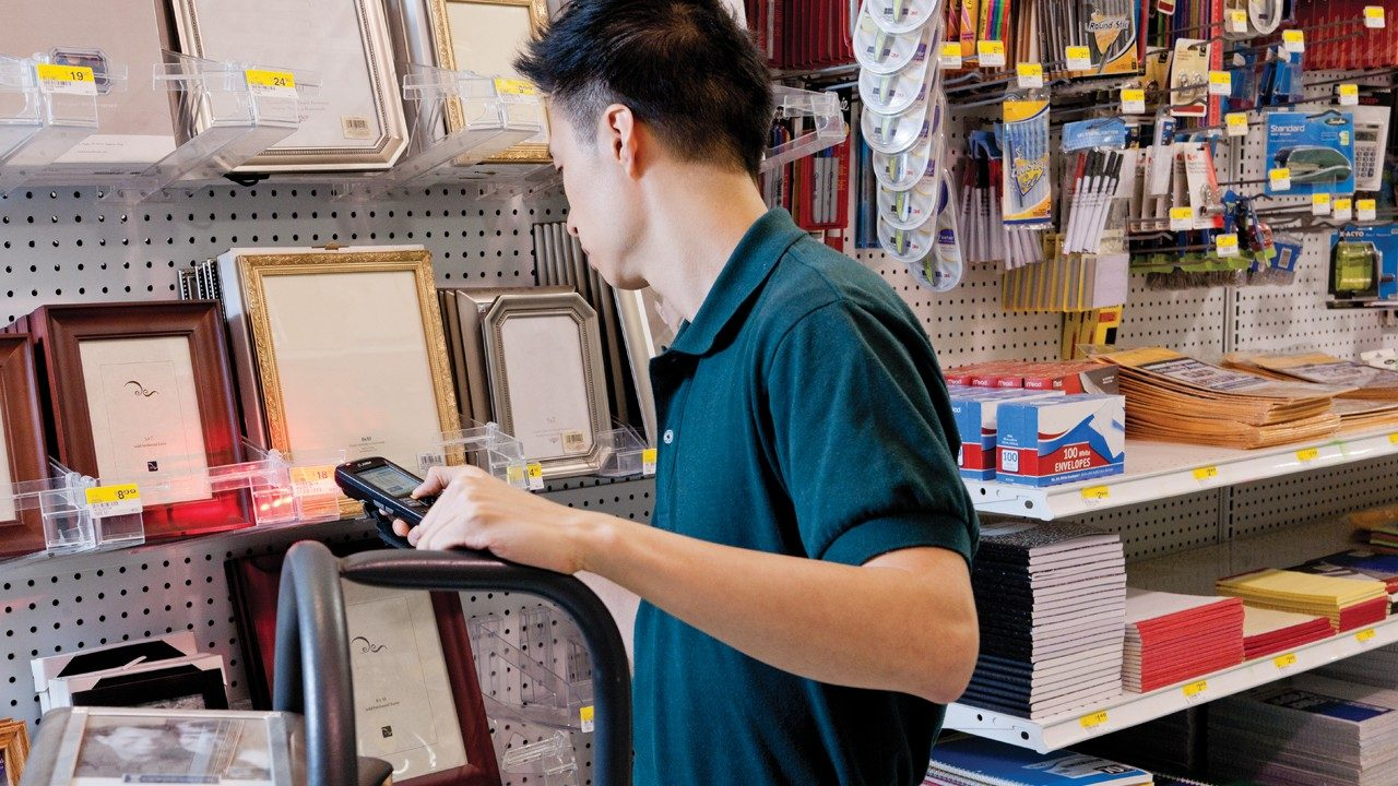 A retail associate uses a handheld mobile computer to scan shelf inventory.