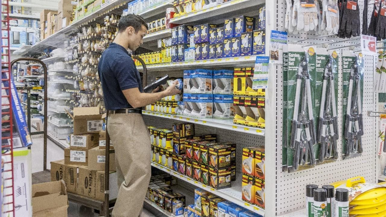 A male stores associate scans cans off vegetables while managing inventory