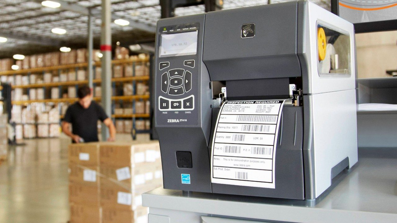 A Zebra ZT400\u002Dseries industrial thermal transfer printer printing a label in a warehouse