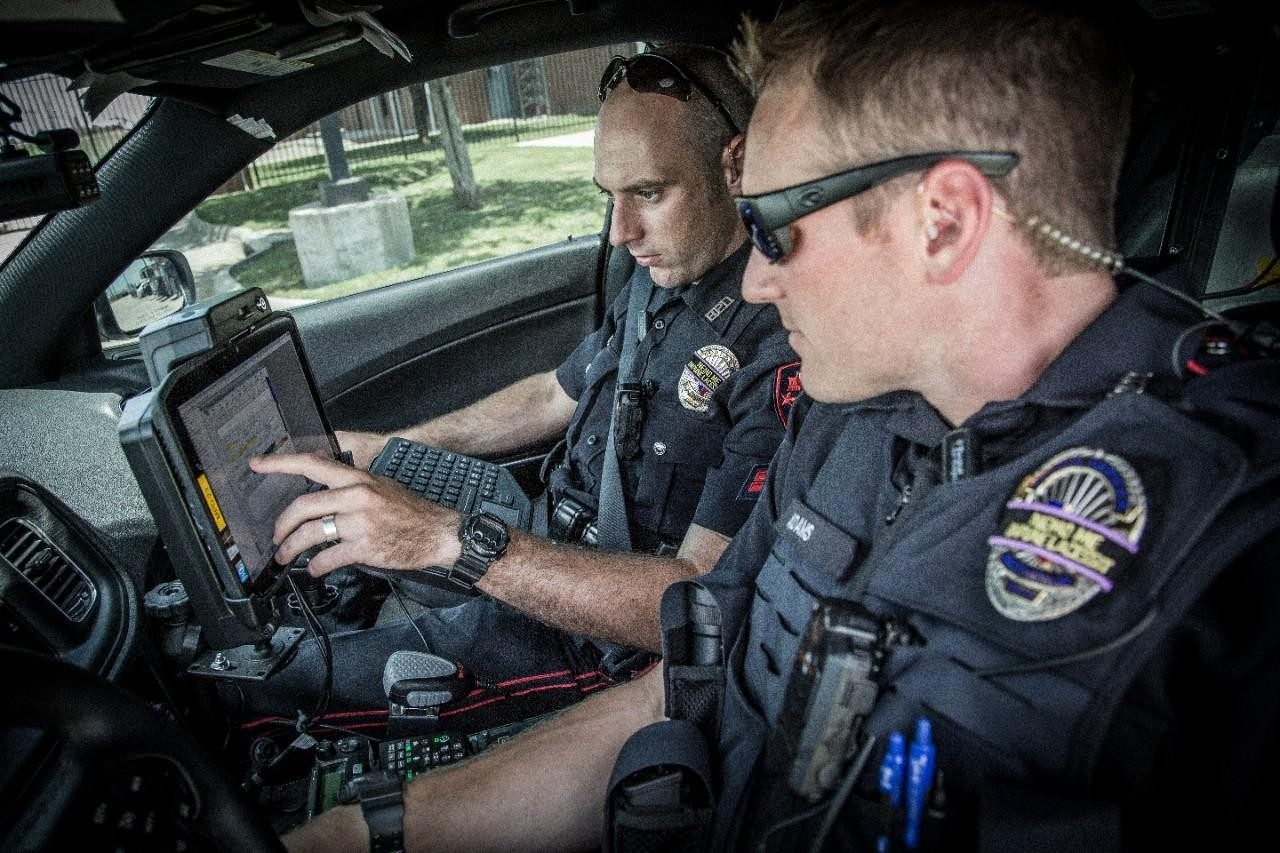 Two police officers look at a rugged tablet mounted in their vehicle for guidance en\u002Droute to a call.