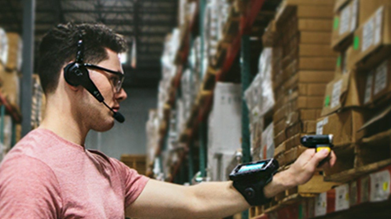 A male warehouse worker uses a headset, wearable mobile computer on his wrist and a handheld scanner to confirm inventory on a shelf.