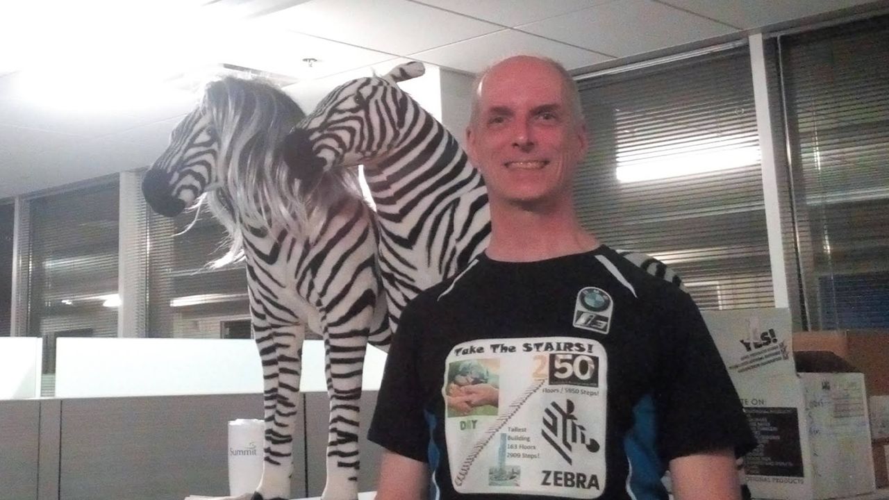 Dave Dipert, Senior Electronics Engineer at Zebra, standing in front of two toy zebras