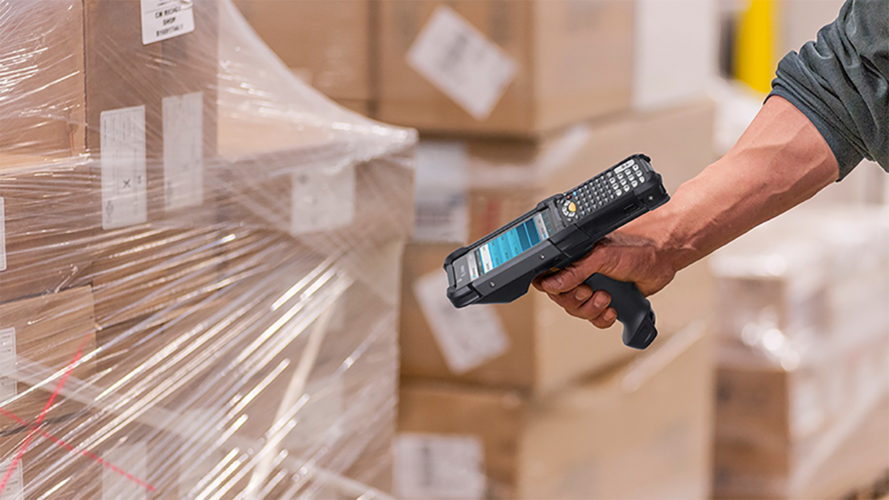 A warehouse worker uses a Zebra MC9300 handheld mobile computer to scan a pallet.