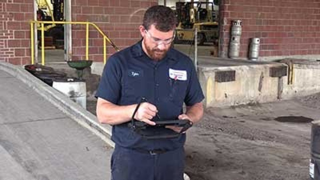 An MH Equipment workers looks at a Zebra rugged tablet that he`s holding on the loading dock