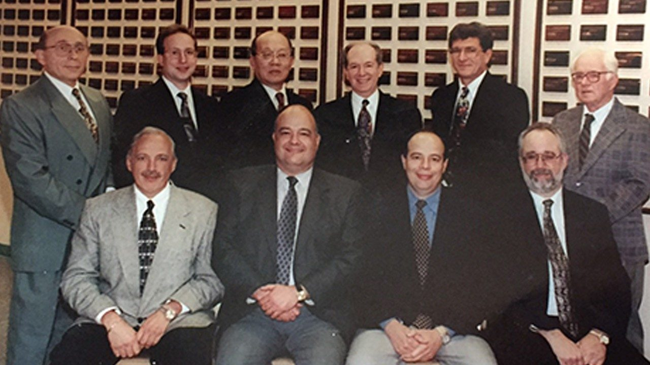 Founder and employees of Symbol Technologies seated and standing circa 1998