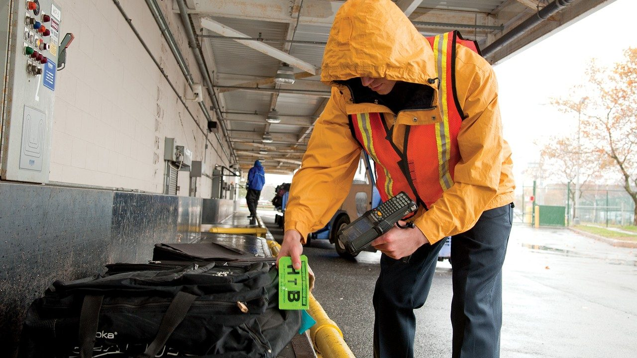 A baggage handler uses a handheld scanner to notate the location of a bag in transit to its next destination.