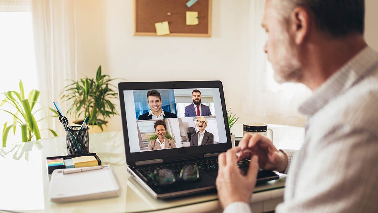 A man working from home participates in a video conference with four other people.
