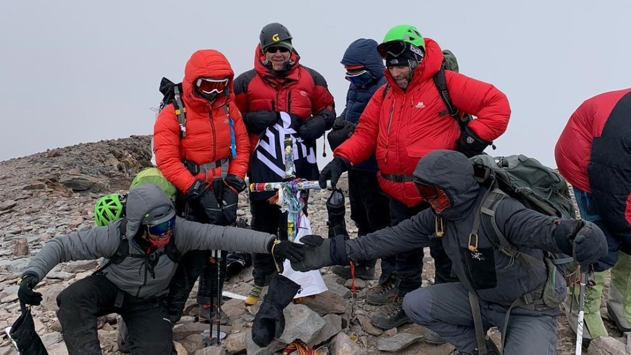 Simon Wallis, Mark Thomson and Jason Harvey celebrate with their guides and teammates after successfully summiting Mount Aconcagua