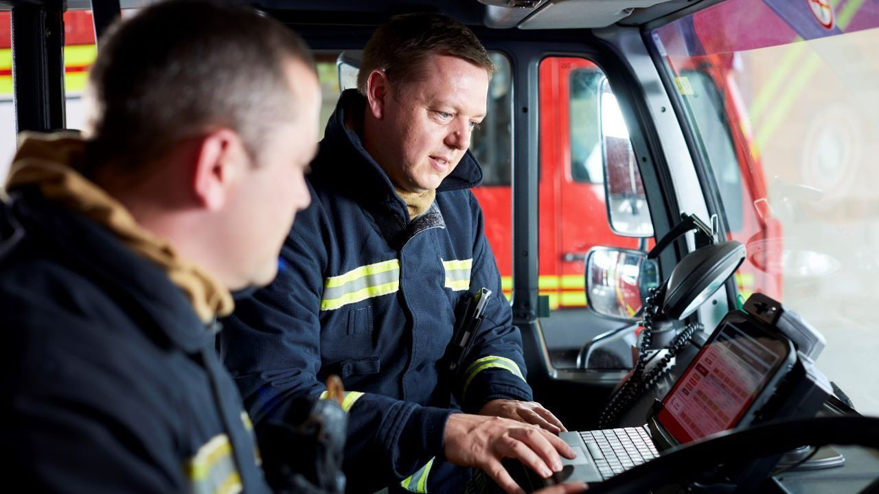 Firefighters look at a rugged tablet mounted in their fire truck