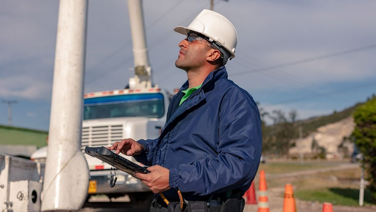 A utility worker uses a rugged tablet to locate an asset in the field