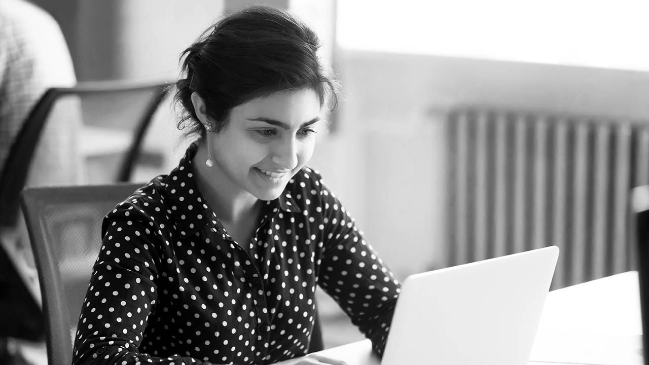A woman smiles while looking at her laptop
