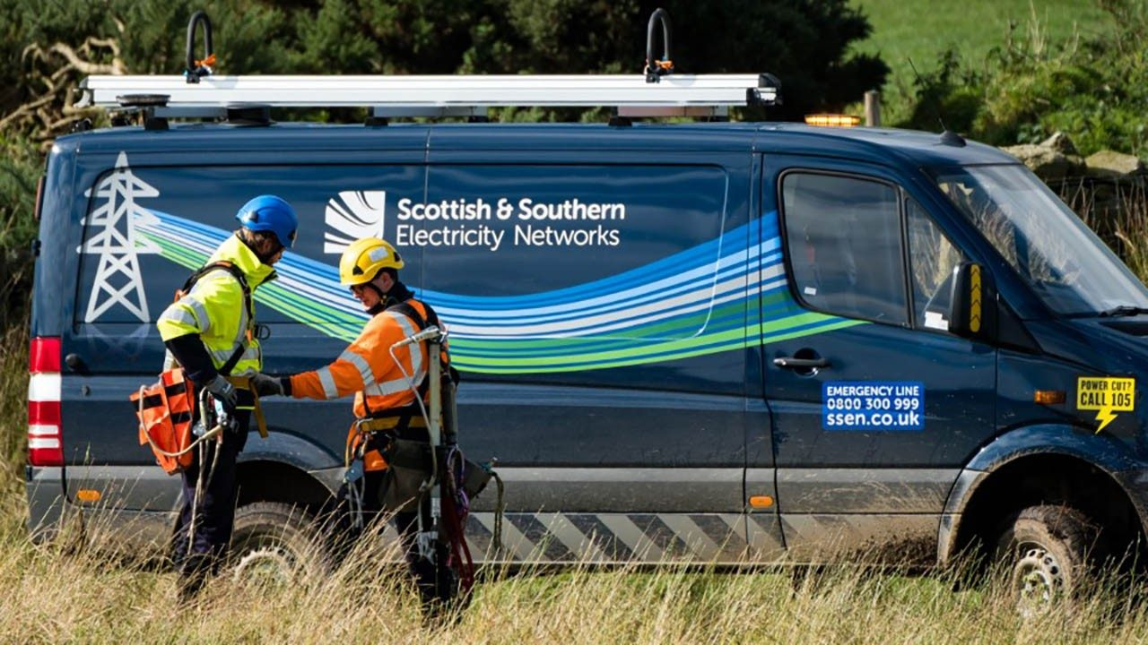 Scottish and Southern Electricity Network workers stand outside their vehicle