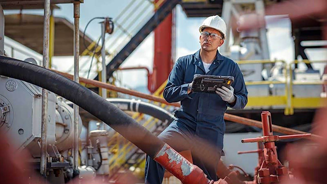 An oil industry worker looks at equipment while holding a Zebra rugged tablet