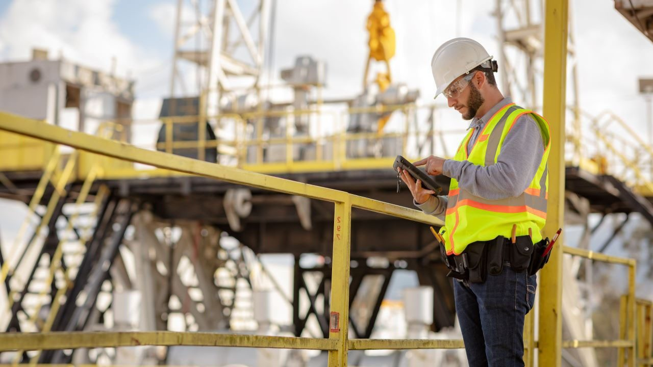 A utility field technician looks at his tablet while standing on a catwalk