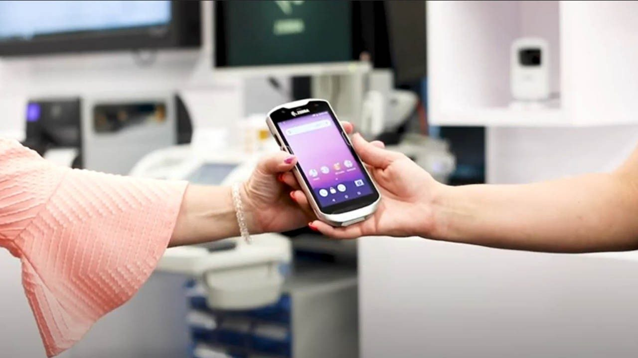 A healthcare provider hands a clinical smartphone off to another worker