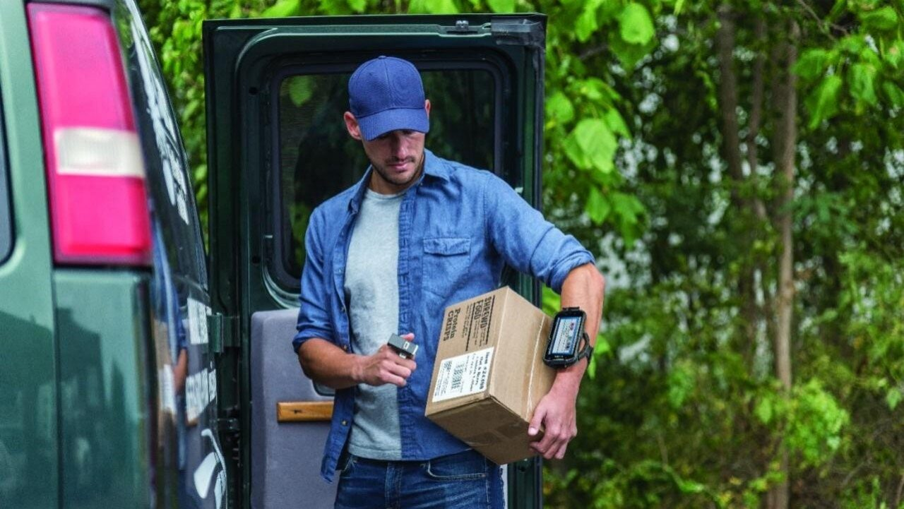A delivery driver scans a package using a ring scanner connected to a Zebra TC52 Android touch computer that he`s wearing on his arm.