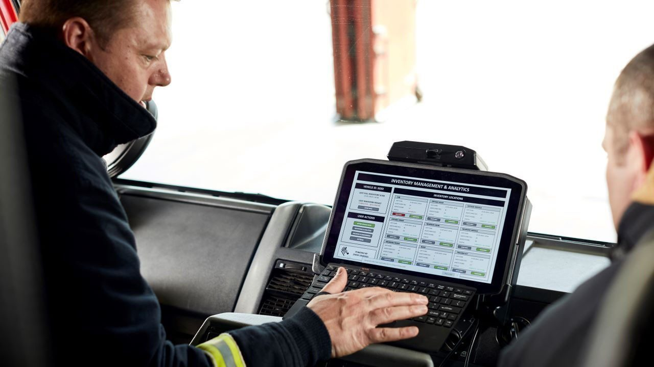 Two firefighters look at a rugged tablet mounted in the console of their truck.