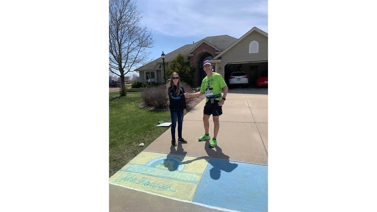 Joe Zons` daughter presents him with his trophy after running a DIY marathon in his hometown