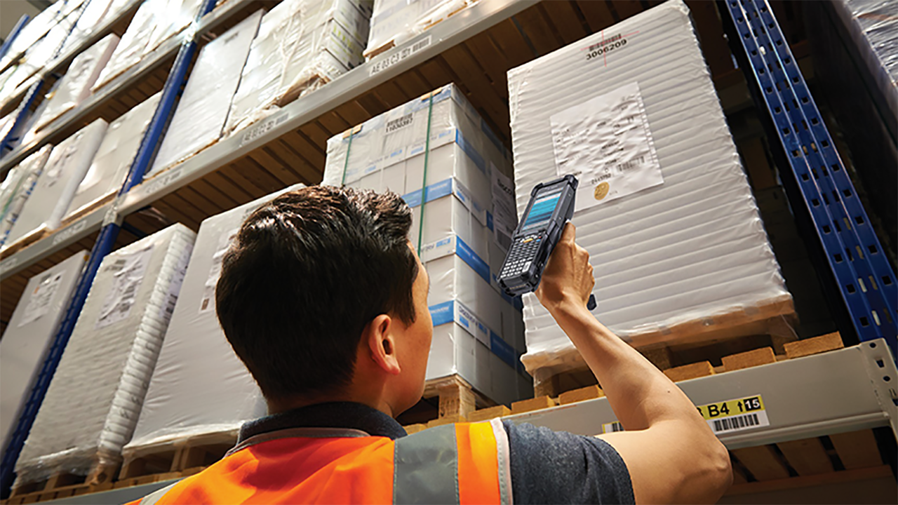 A warehouse workers uses the Zebra MC9300 hybrid handheld mobile computer to scan the label of an item on a high shelf.