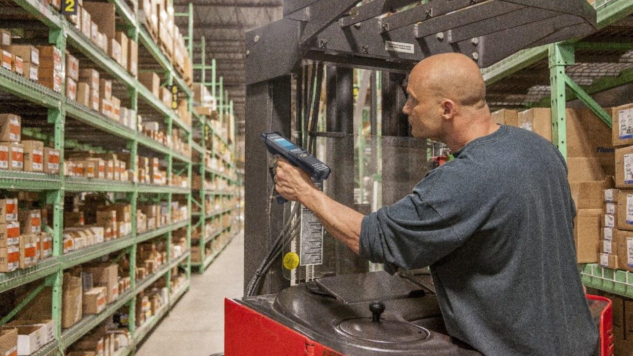 A male warehouse worker uses a handheld mobile computer to scan an item on a shelf