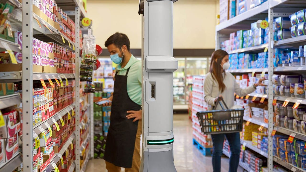 The Zebra EMA 50 enterprise mobile automation system navigates around two grocery store associates and a shopper in an aisle