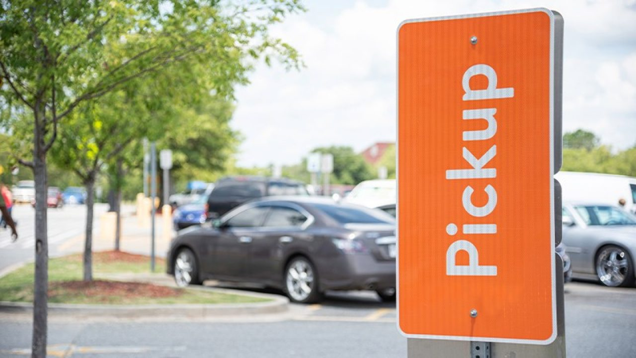 Orange retail curbside pickup sign in a parking lot