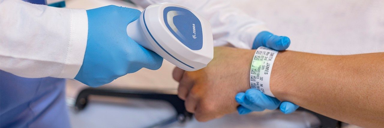 Hospital employee scanning a patient`s wristband using a Zebra barcode scanner.