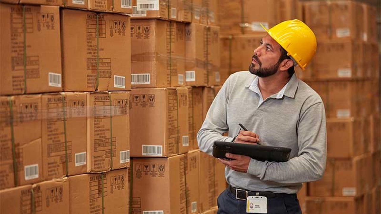 Worker taking inventory in Warehouse with Zebra tablet