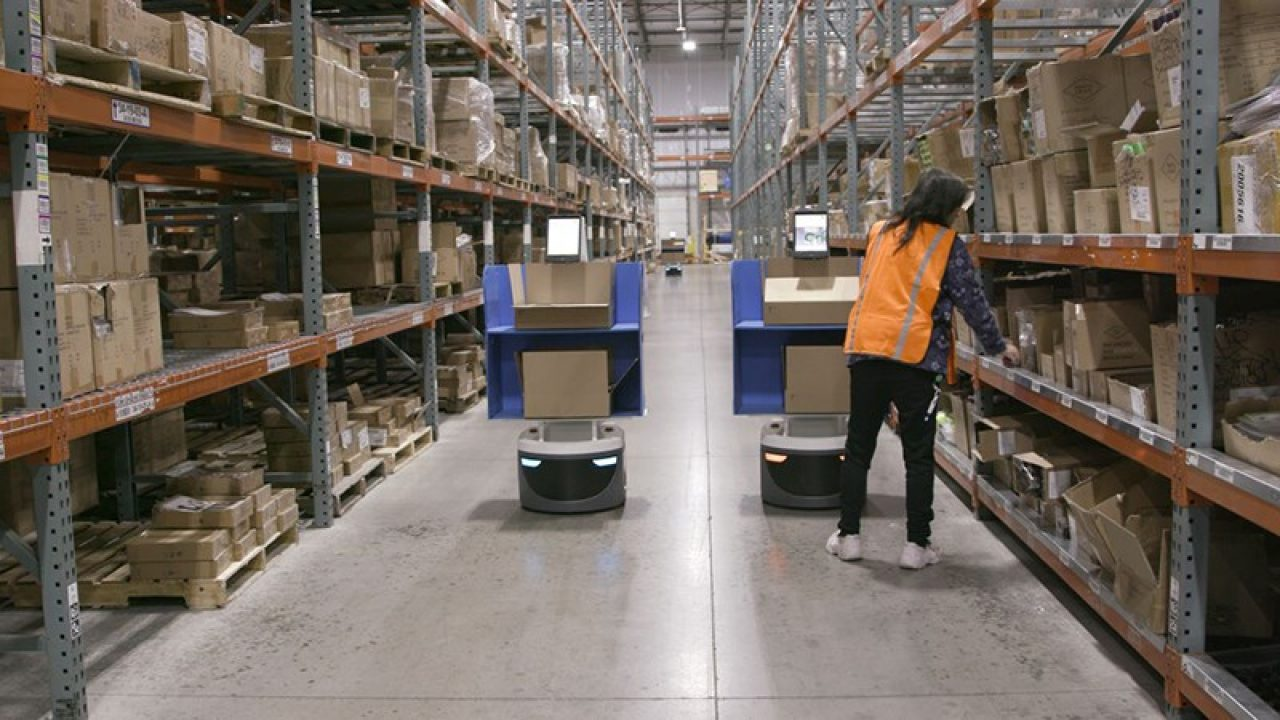 Worker in warehouse aisle with robots