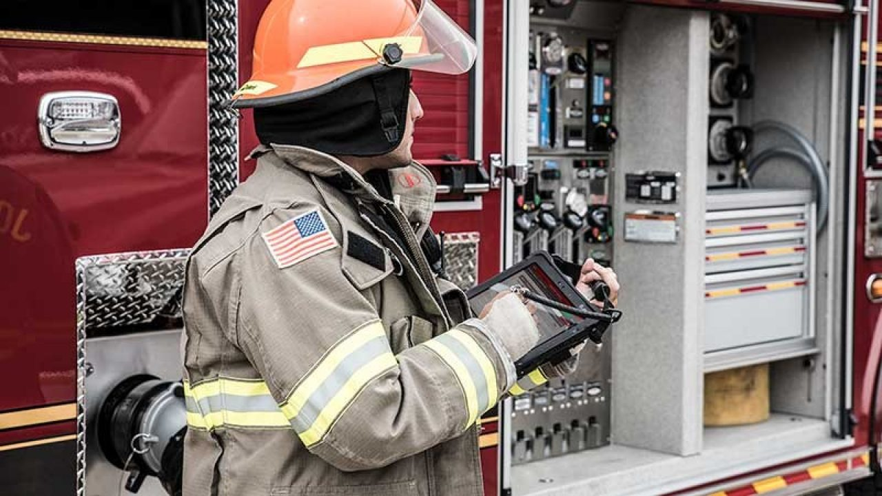 Firefighter working on a tablet in front of a fire truck