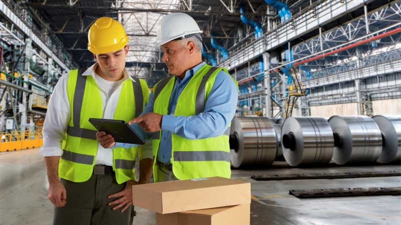 Man training another man on a tablet in a manufacturing plant