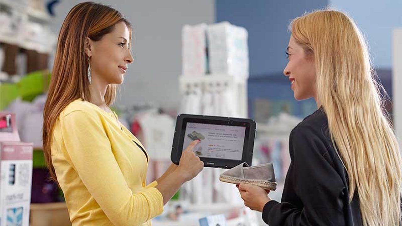 Retail worker assisting a customer with a Zebra tablet.