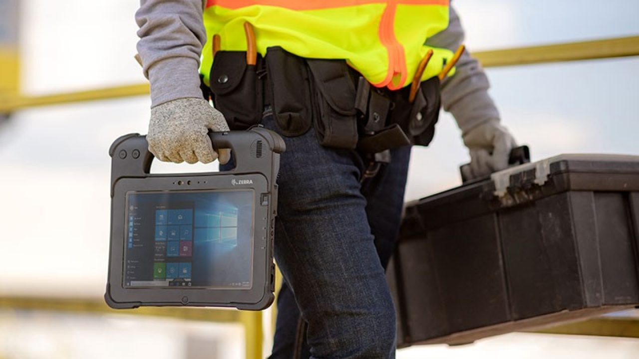 Energy company employee carrying a tablet and toolbox.