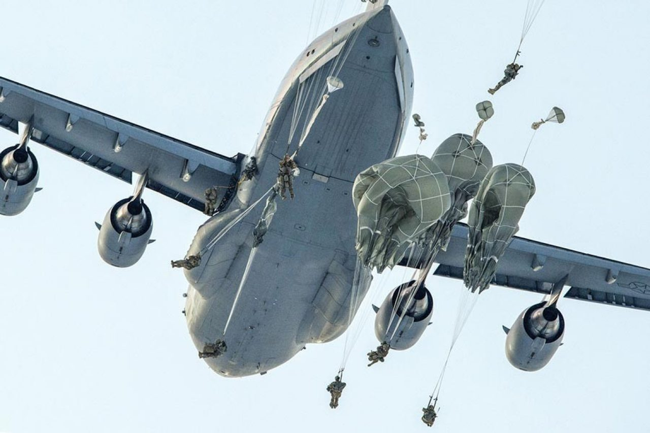 military personnel jumping out of airplane with parachutes