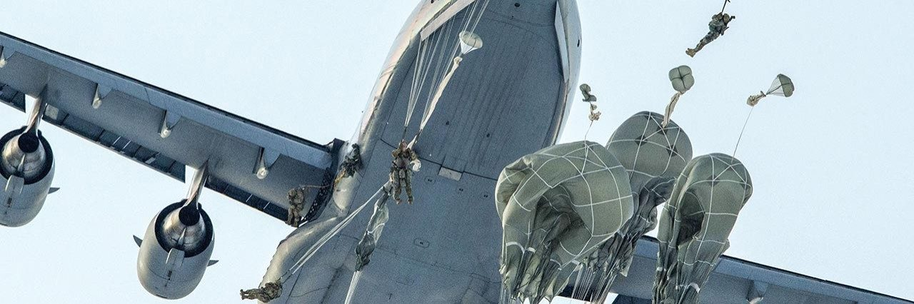 military personnel jumping out of plane with parachutes