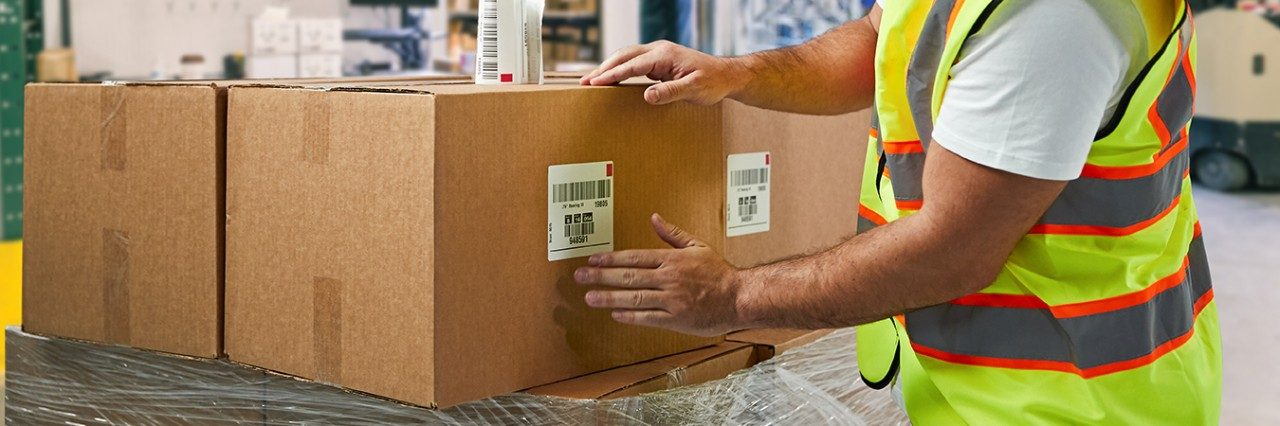 warehouse associate adding a barcode package label to a box