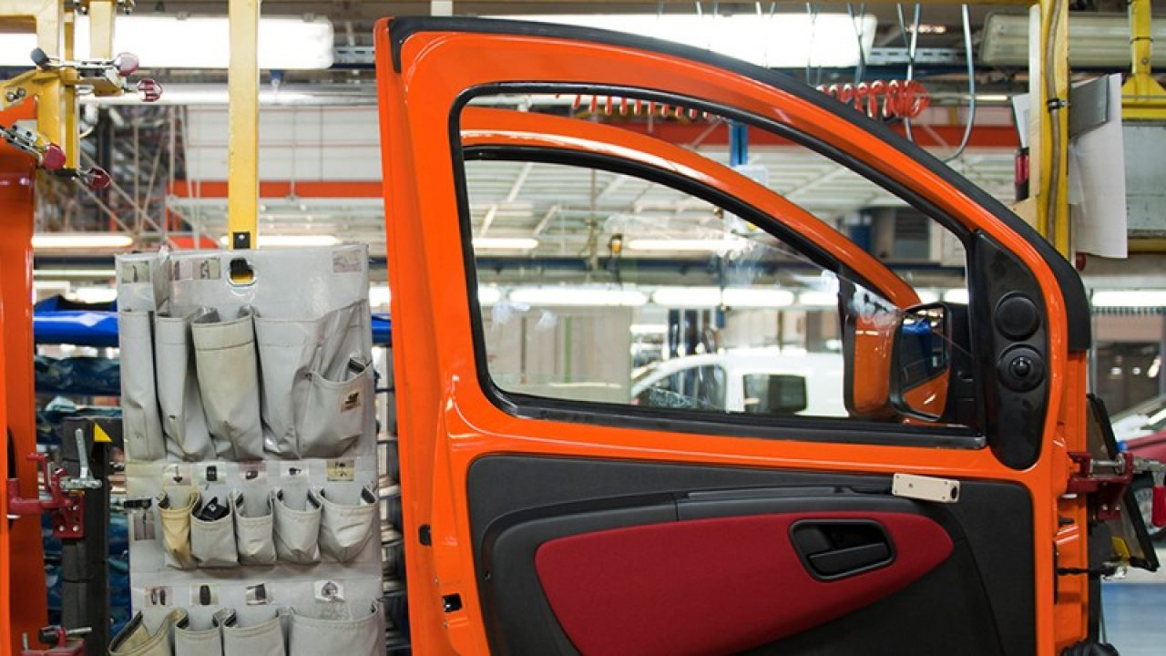 Car being manufactured in a manufacturing plant.