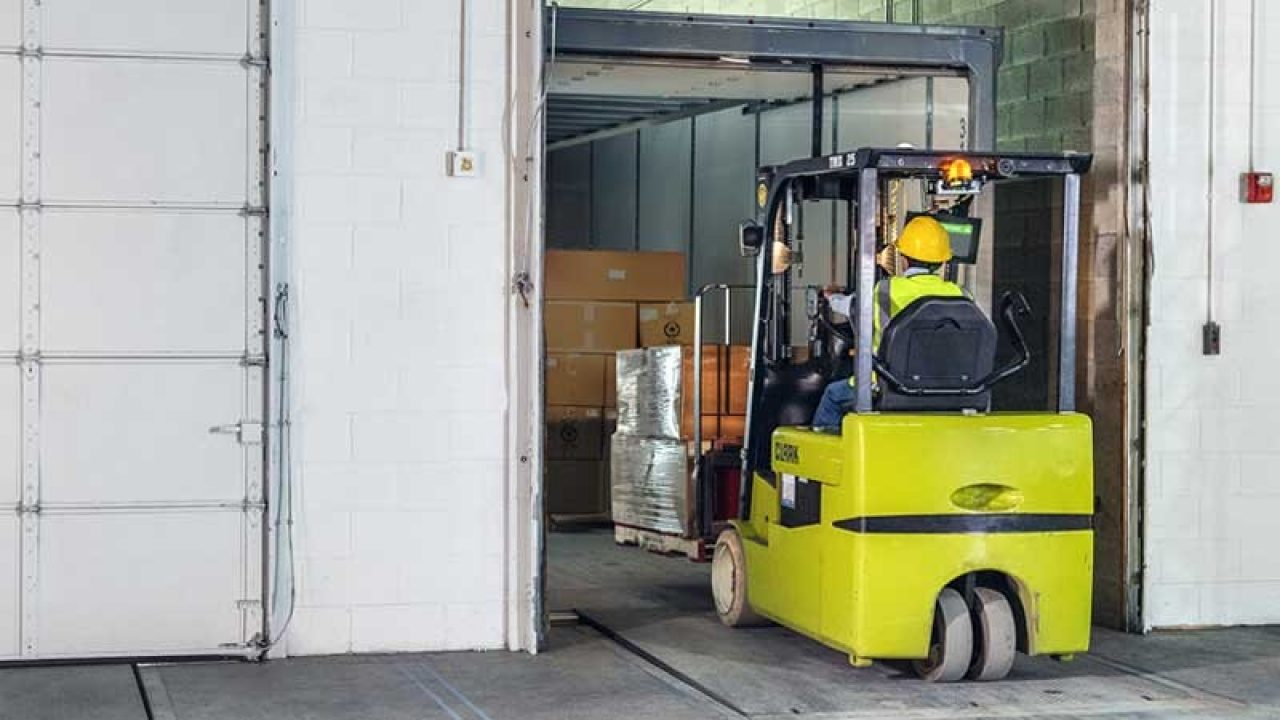 Warehouse employee on a forlift driving into the warehouse